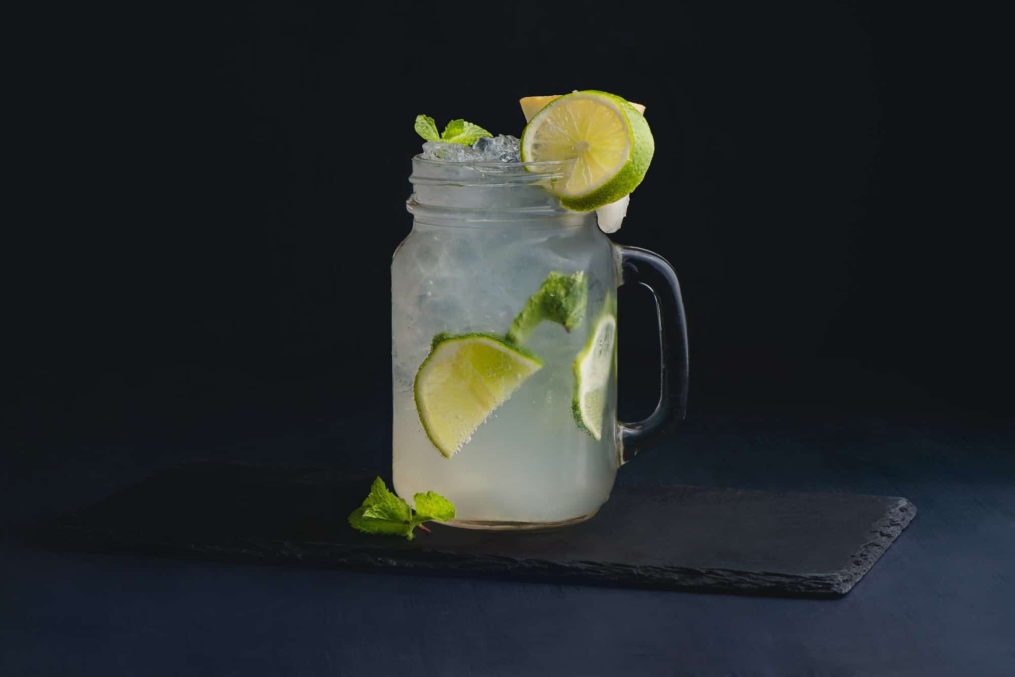Ice cold classic lime lemonade in a vintage glass mason jar. Dark background with copy space for a